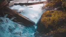 Rushing Water Rapids Running Through Log Chute And Crashing Into Damaged Moss Covered Log Chute Wooden Beams While Spraying Mist And Water Onto Moss-Covered Rocks During Autumn 4K ProRes