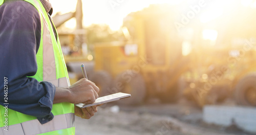 Obraz Asian engineer with hardhat using  tablet pc computer inspecting and working at construction site - fototapety do salonu