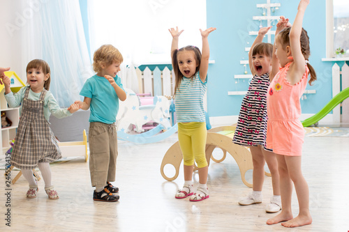 Group of expressive preschool children with raising hands while having fun in entertainment center