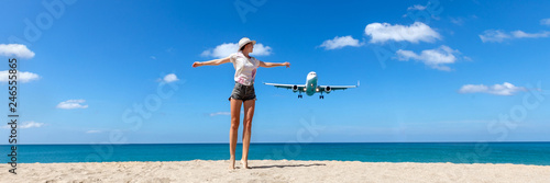 Girl looking at the flying plane above the sea, travel and active lifestyle concept
