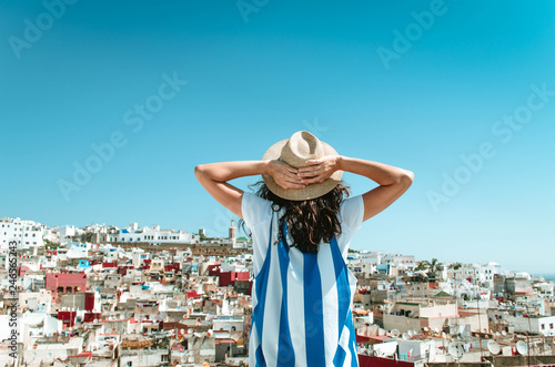 Poster Maroc Tourist on vacation in Morocco. Woman with expression of freedom and enjoyment. Girl with hut and white and blue dress on a Tangier terrace