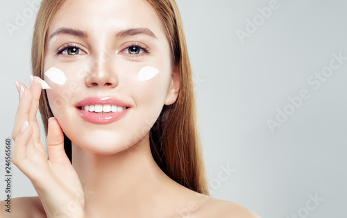Photo Closeup portrait of beautiful woman with healthy face and skin applying cosmetic cream
