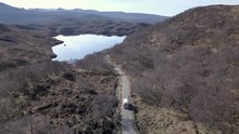 Aerial Footage Of A Vintage Campervan Driving Down A Country Road On A Sunny Day In Assynt, Scottish Highlands, Scotland