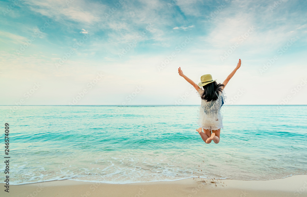 Fototapeta Happy young woman in casual style fashion and straw hat jumping at sand beach. Relaxing, fun, and enjoy holiday at tropical paradise beach with blue sky and white clouds. Girl in summer vacation.