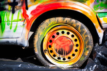Shot Of Colorfully Painted Car Tire On An Old, Crashed Car Wreck. Kids Are Having Fun, Making Drawings And Graffiti Art, Paint On Wreck And Tires With Green, Red, Orange, Yellow, Blue Colors