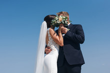 The Bride And Groom Kiss Hidin...