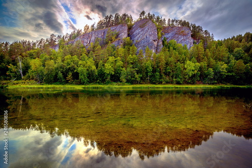 Fotografia  Reflection of a picturesque rock in the water of a river