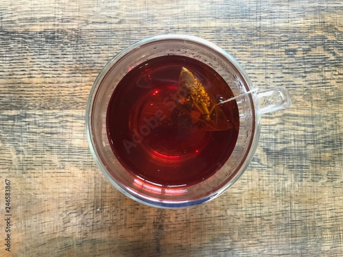 Fotografía  Oversight of Infusion of rooibos in a cup of clear glass over a background of ol