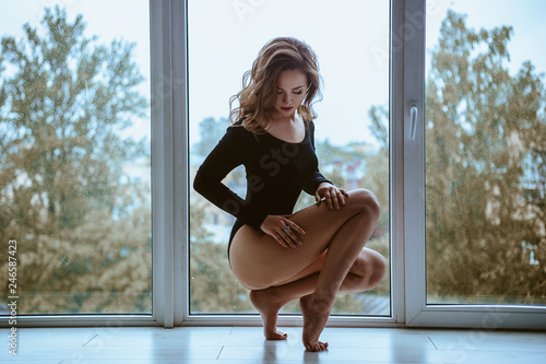 Young woman with perfect figure posing near panoramic window Canvas-taulu