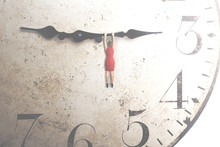 Business Woman Trying To Stop The Time Hanging On The Hand Of A Clock