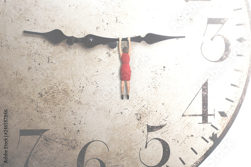 Obraz   business woman trying to stop the time hanging on the hand of a clock - fototapety do salonu