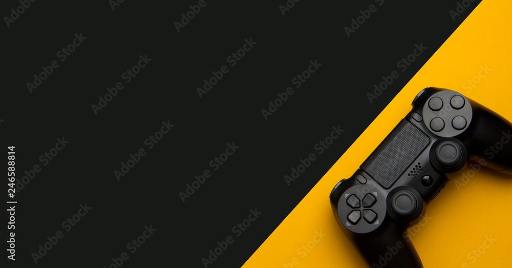 Fototapeta black wireless gamepad on a black and yellow background