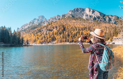 Poster Salmon Traveler Woman use mobile phone to take amazing photos of a Misurina mountains lake