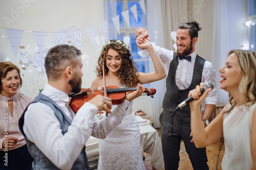 Photo A young bride, groom and other guests dancing and singing on a wedding reception