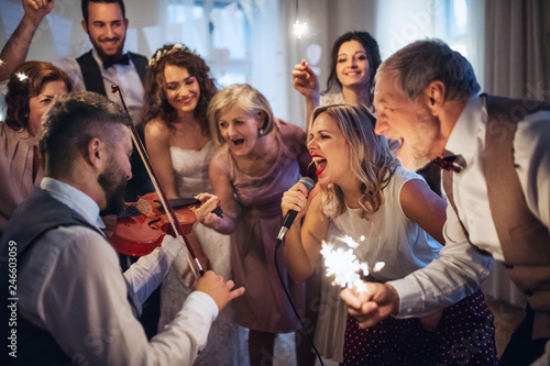Fotografia  A young bride, groom and other guests dancing and singing on a wedding reception