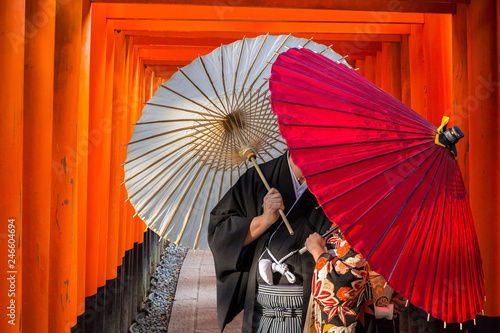 Deurstickers Asia land Couple with traditional japanese umbrellas posing at torii gates in Kyoto