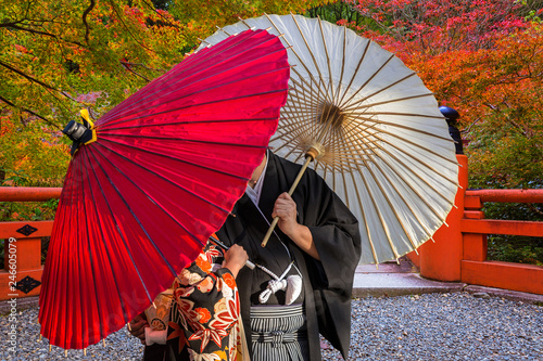 Deurstickers Asia land Couple with traditional japanese umbrellas posing at autumnal park in Kyoto