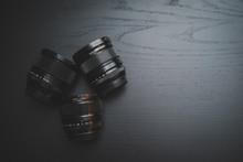 Camera Lens On Dark Wooden Desk