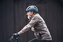 Active Senior Man With Bike Helmet Cycling Outdoors Againts Dark Background.