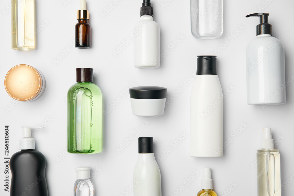 Fototapeta Top view of different cosmetic bottles and container on white background