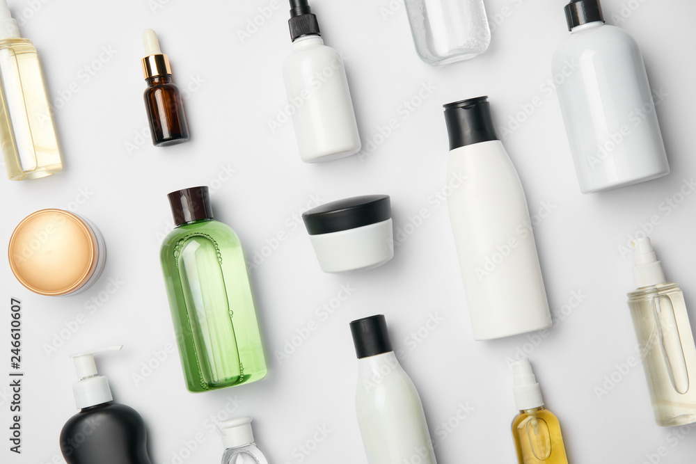 Fototapeta Top view of various cosmetic bottles and containers on white background