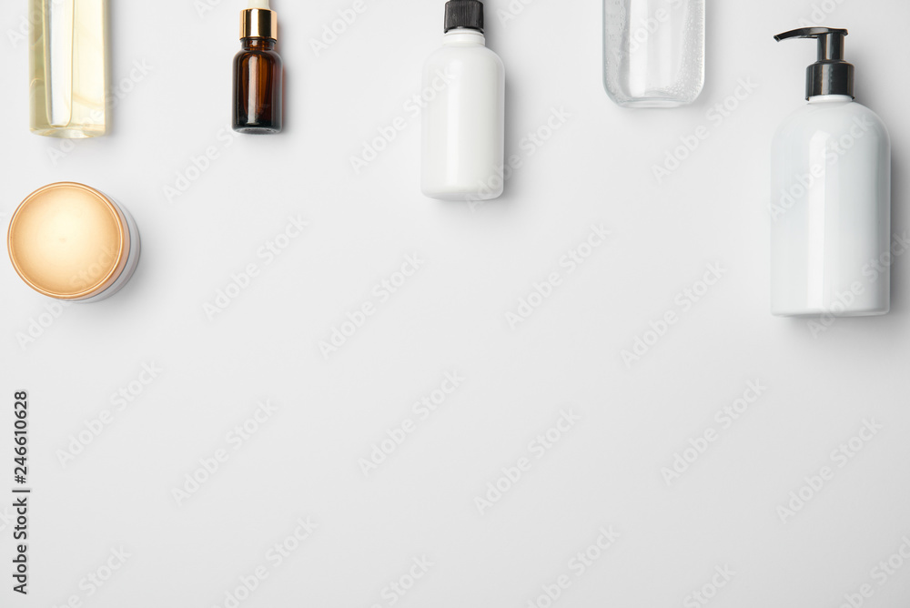 Fototapeta Top view of different cosmetic bottles on white background with copy space
