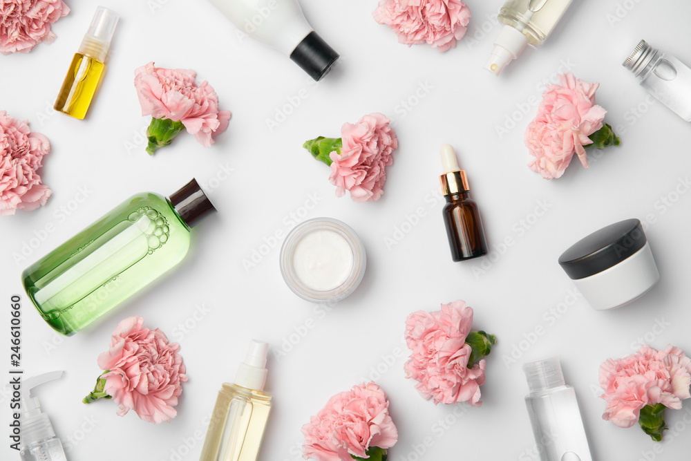 Fototapeta Top view of various cosmetic containers and pink carnations flowers on white background