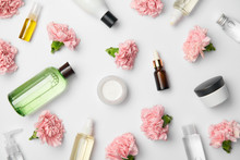 Top View Of Various Cosmetic Containers And Pink Carnations Flowers On White Background