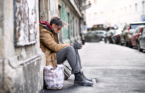 Foto Homeless beggar man sitting outdoors in city asking for money donation