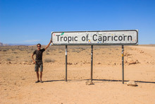 White Caucasian Male Traveler In Sportswear Standing Next To The Tropic Capricorn Sign In Sosusflei National Park In Namibia