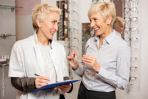 Fotografía  Happy senior female patient consulting with mature optometrist who is holding a
