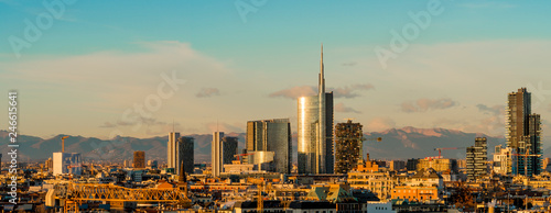Aerial view of Milan skyline at sunset with alps mountains in the background.