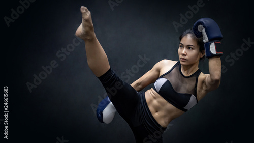 Photo Stands Martial arts Young Asian woman boxer with blue boxing gloves kicking in the exercise gym, Martial arts on black background. Female boxing class concept