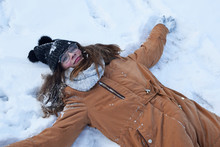Teenage Girl Wearing Glasses And Knitted Hat Lying Down On White Snow With Raised Hands Making Snow Angel And Enjoying Snowy Weather. Youngsters Outdoor Activities In Xmas Holidays.