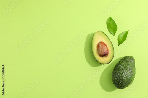 Tablou Canvas Ripe sliced avocado with green leaves, top view