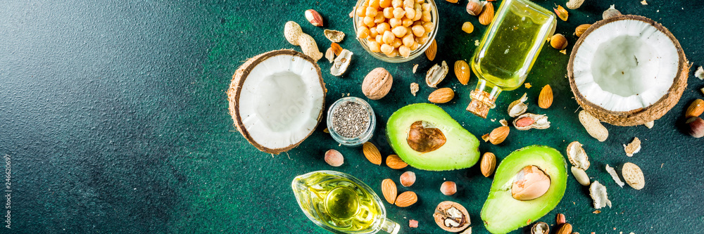 Fototapeta Healthy vegan fat food sources, omega3, omega6 ingredients - almond, pecan, hazelnuts, walnuts, olive oil, chia seeds, avocado, coconut,  banner copy space