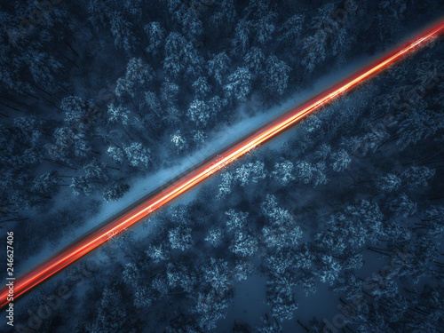 Aerial view of night winter road and cars passing by forest in mountains. drone shot