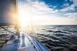 canvas print picture - Sailing at sunset. A view from the yacht's deck to the bow and sails. Baltic sea, Latvia