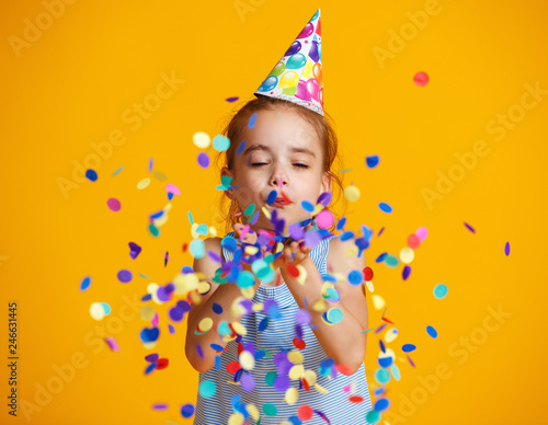 Photo  happy birthday child girl with confetti on yellow background.
