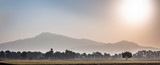 Wide landscape shot of sunrise through mountains in the early morning through fields with mist and fog. - 246634049