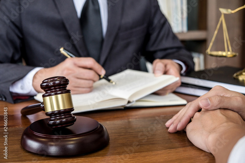 Foto  Judge gavel with scales of justice, Businesswoman and male lawyers or counselor discussing contract papers at law firm in office