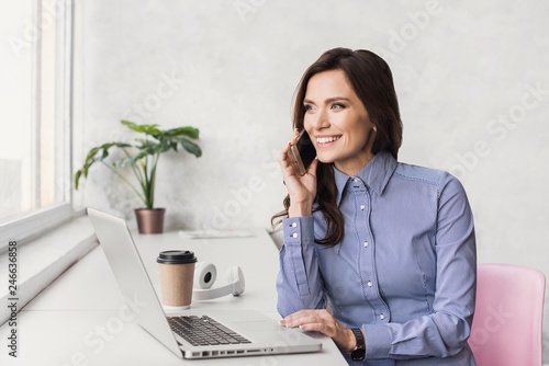 Fotografie, Obraz  Business woman using laptop and talking on smart phone
