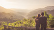 Traveler hike and camping in summer concept, Back side of romantic Asian young couple see view sunrise and breathe fresh air top of mountain in tropical forest background.