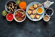 Brunch or breakfast concept on dark background. Valentine's Day or Mather's Day. Healthy breakfast fried eggs, salad, pancakes, juice, coffee, granola and dried fruits. Top view with copy space.