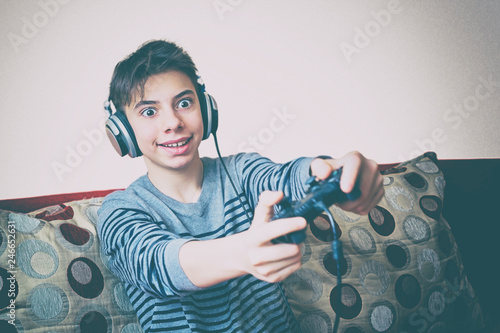 Fotografía  teenage boy with headphones on his head emotionally playing game console sitting