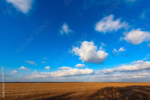 White clouds are crossing blue sky over plain landscape