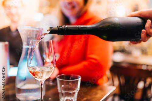 Poster de jardin Bar Waiter pouring wine in glass for guests at table in bar restaurant party