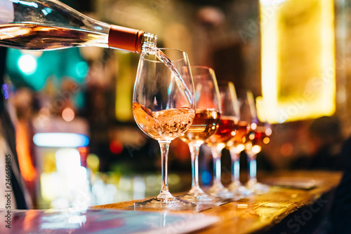Fotobehang Alcohol Service Serving Pouring Wine in shiny glasses in bar restaurant night club