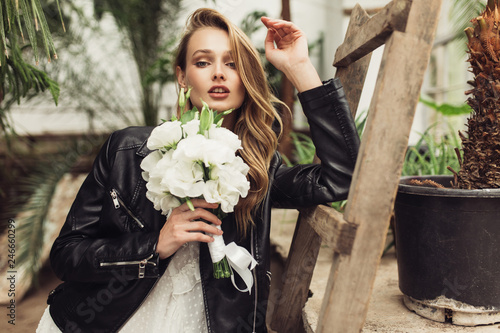 Fotografía  Young beautiful woman in black leather jacket and white dress holding little bou