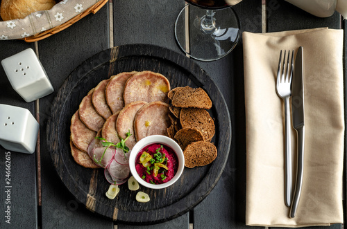 Fotografía  Snack from the tongue with croutons and horseradish on a dark background